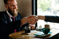 businessman suit and tie shaking hands in cafe